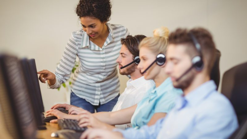 Businesswoman guiding employee in call center