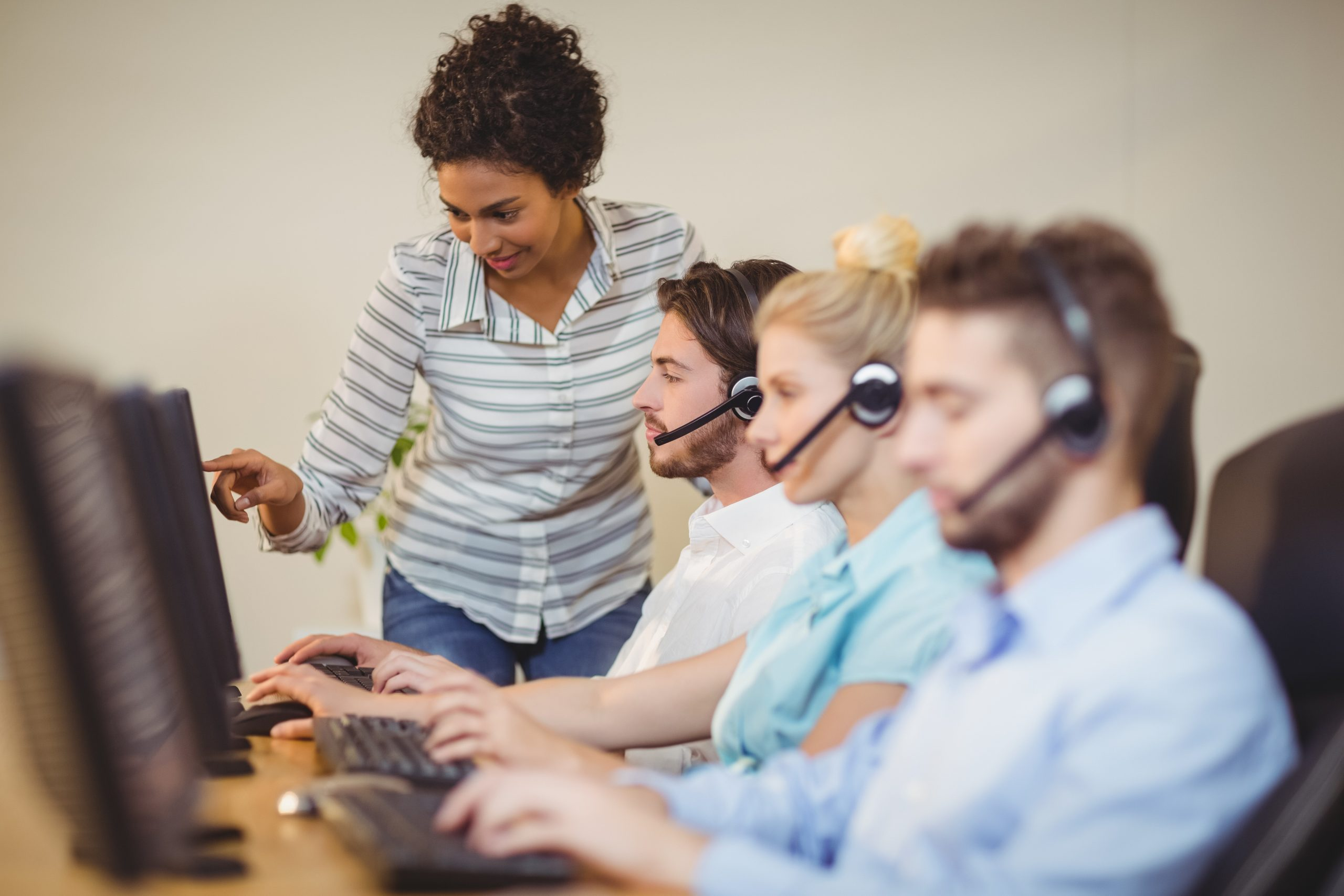 Businesswoman guiding employee in call center