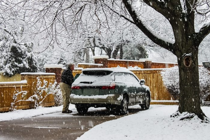 Middle aged man with snow covered car in driveway on extremely snowy day with snow falling