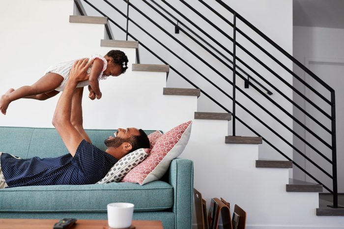 Father Lying On Sofa At Home Lifting Baby Daughter Into Air