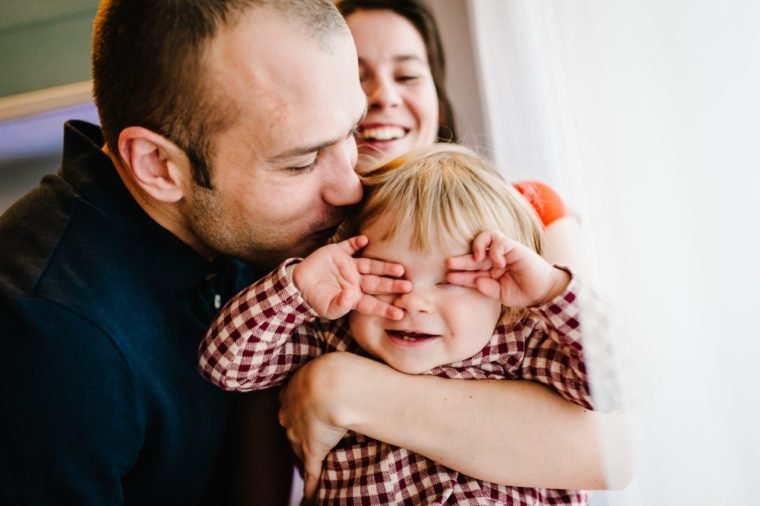 The father, mother holds little girl on background white wall indoor. Portrait of dad and daughter. The concept of family holiday. She closed eyes with hands and showed teeth. upper half. Close up.