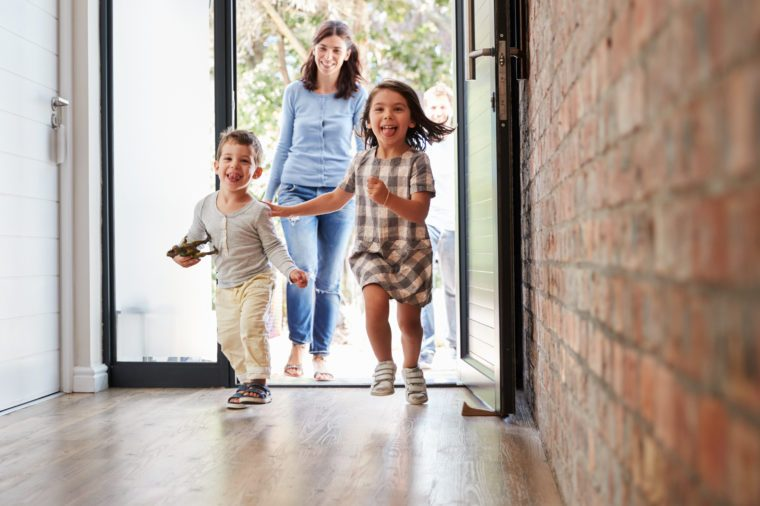 Excited Children Arriving Home With Parents