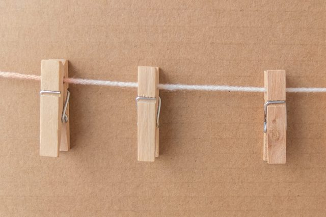 clothespins attached to a rope on brown paper background with clipping path