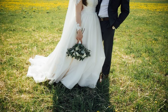 portrait of beautiful bride with wedding bouquet isolated at green natural summer field background.
