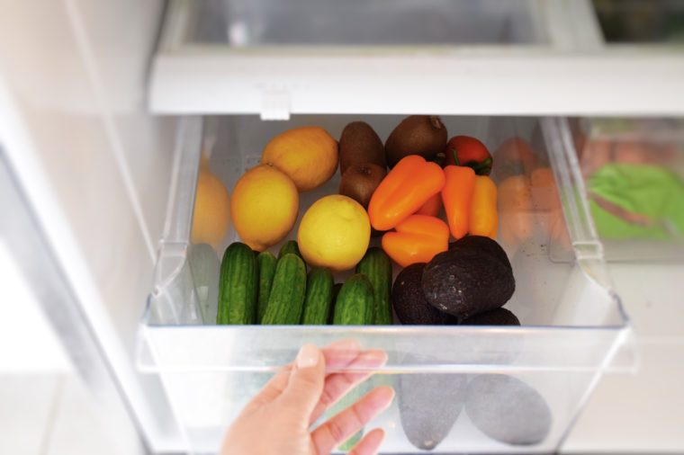 Female hand taking vegetables from a crisper drawer of a refrigerator