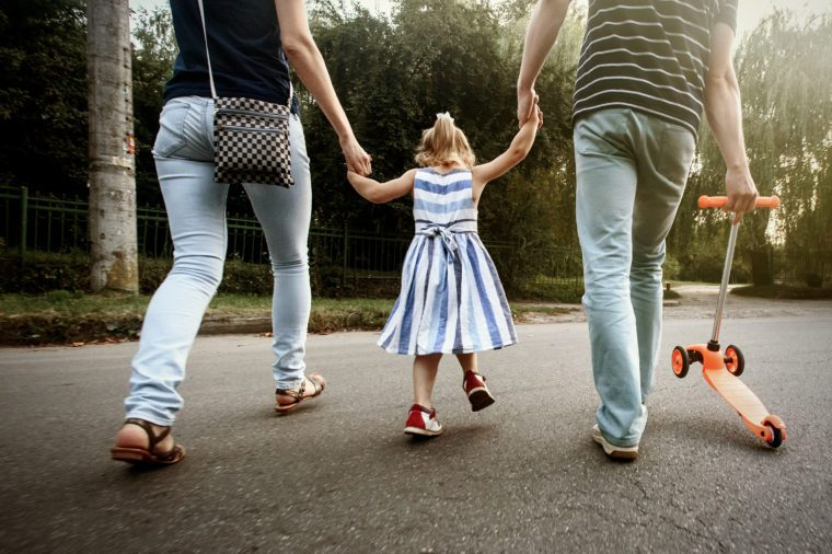 happy stylish parents holding hands with daughter and walking in sunny street, amazing family moment. father's mother's day