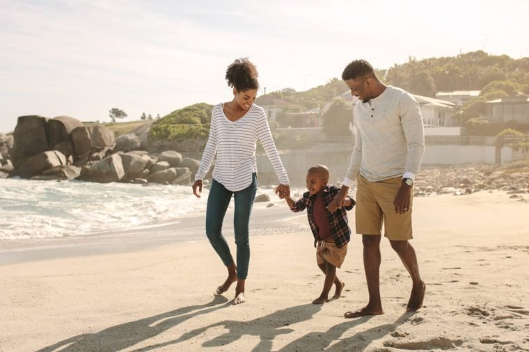 Family of three taking a walk along the sea shore. Man and woman holding hands of son and walking on beach.