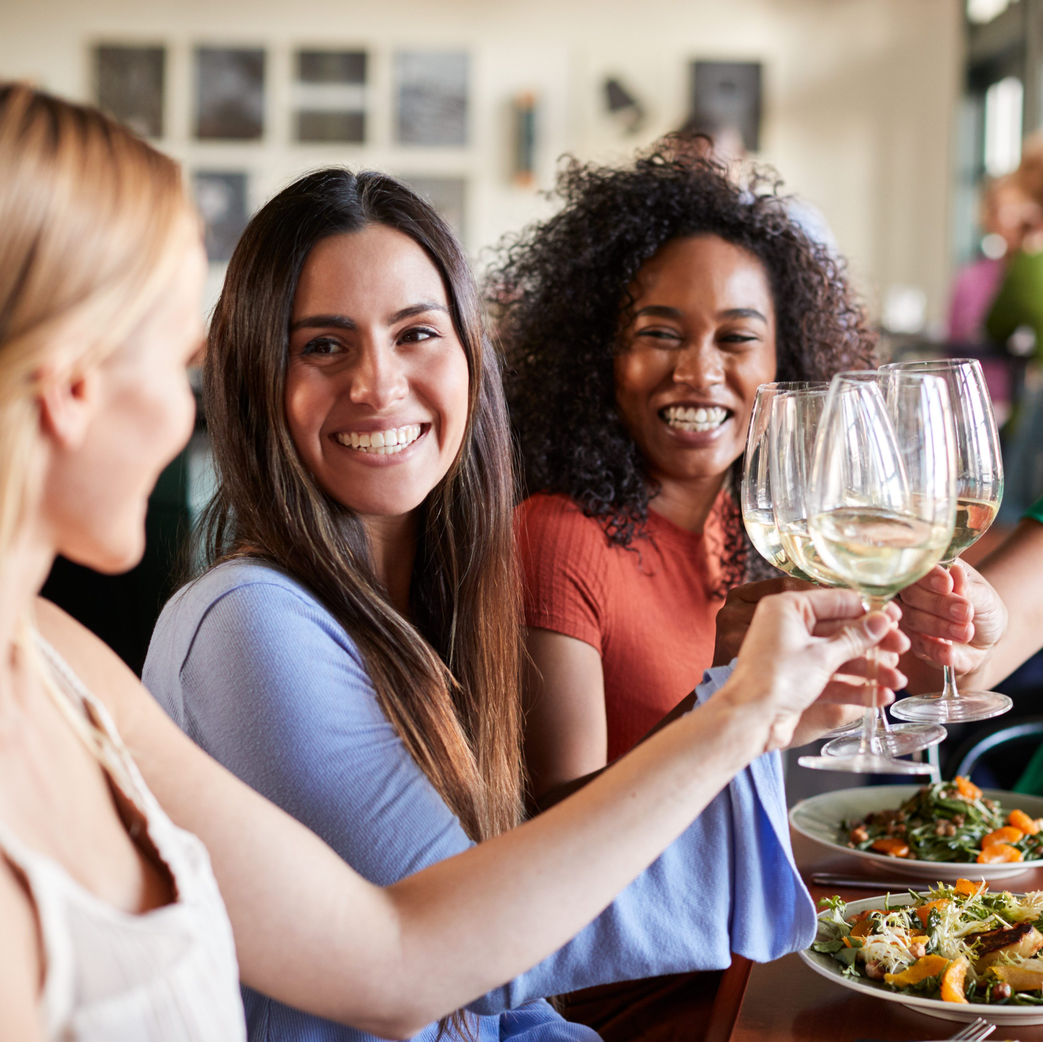 Group Of Female Friends Making A Toast At Meal In Restaurant