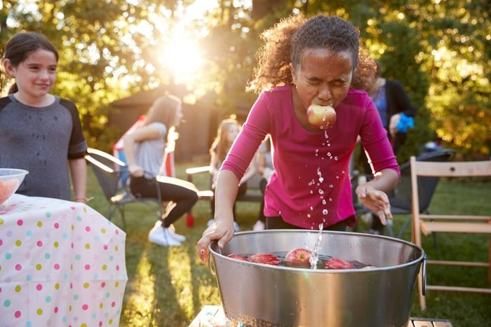 Pre-teen girl, apple in mouth, apple bobbing at garden party