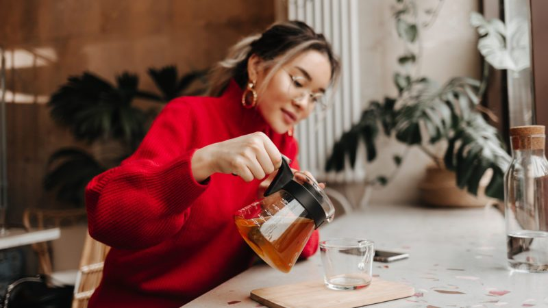 Snapshot of Asian girl in red outfit pouring herself green tea in cup while sitting in cafe
