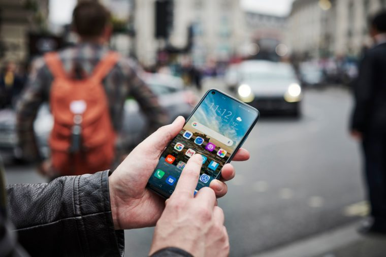 A Man Holding Up An Honor 20 Pro Smartphone