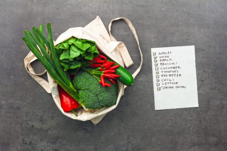 Shopping bag full of vegetables and fruits with checked shopping list. Flat lay food on table.