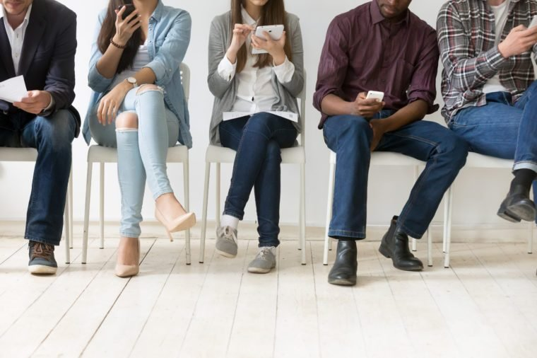 Diverse black and white people sitting in row using smartphones tablets, multiracial men and women waiting for job interview, human resources, employment or customers and electronic devices concept
