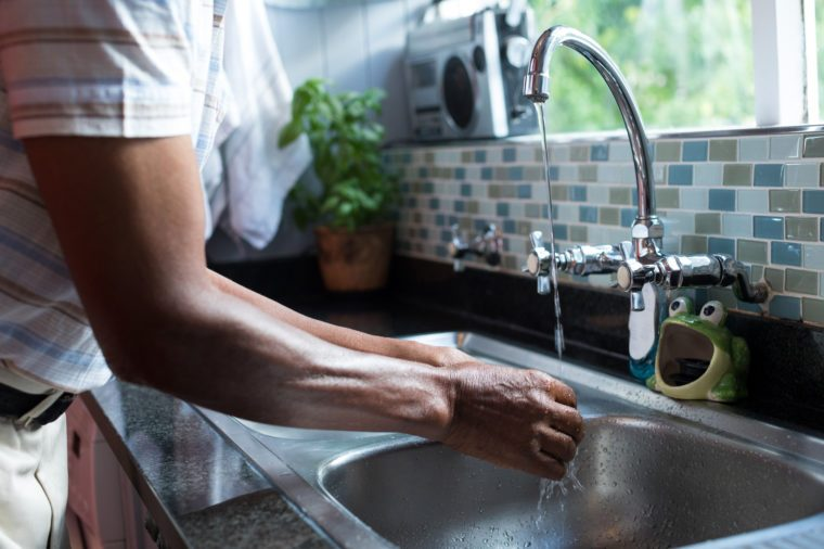 Midsection of man washing hands at sink by window