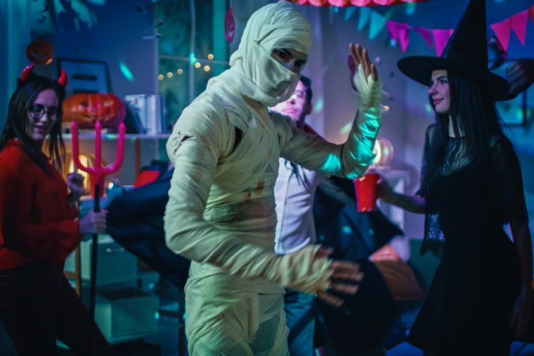 Halloween Costume Party: Old Skinny and Bandaged Mummy Dances. In the Background Zombie, Death, Witch and She Devil Have Fun in a Monster Party Decorated Room