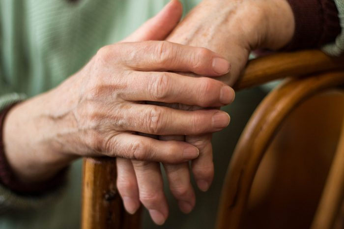 two hands of an elderly woman sitting on a chair