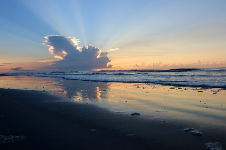 Marine landscape with sunbeams from sun rising from the cloud and beautiful reflection in a shallow ocean water. Huntington Beach State Park, Litchfield, Myrtle Beach area, South Carolina.
