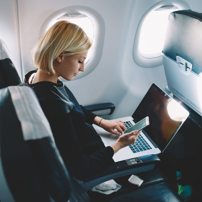 Businesswoman with short haircut sitting in airplane cabin and chatting online on smartphone while checking email on laptop computer with mock up area.Female traveler reading notification on cellular