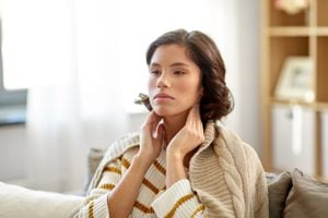 cold and health problem concept - sick woman touching her lymph nodes at home