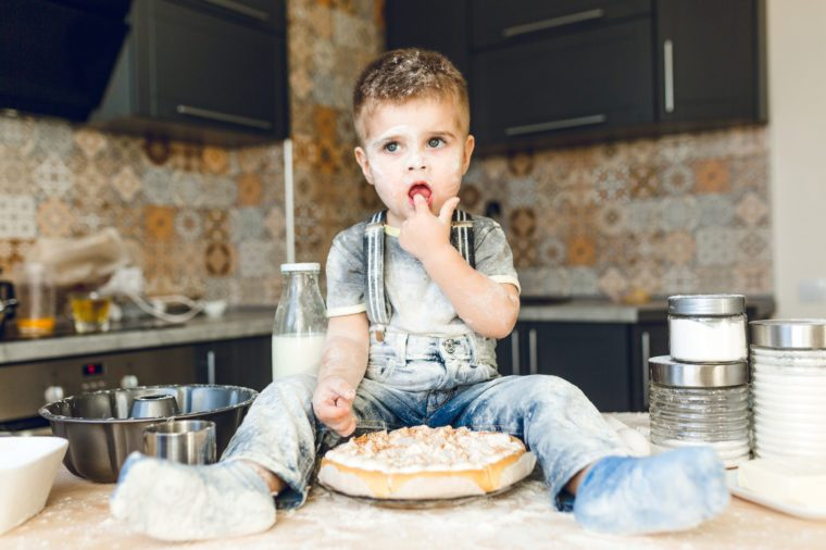 Funny kid sitting on the kitchen table in a roustic kitchen playing with flour and tasting a cake. He is covered in flour and looks funny. He puts his finger in the mouth.