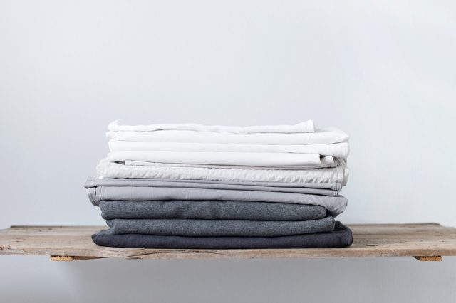 linen textile in stacked pile. sheet and cover. different shades white grey pastel color cloth. background. copy spase