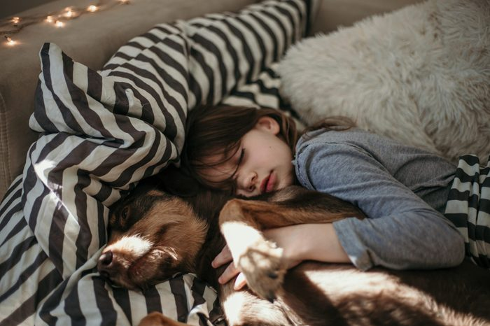 Beautiful girl sleeping with her puppy dog. Cuddling and hugging in the bed