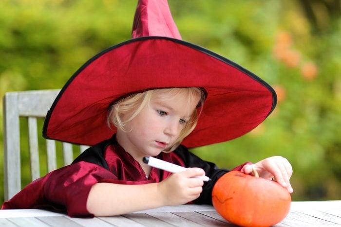 Portrait of little girl in Halloween witch costume decorating pumpkin outdoors in the garden. Kraft for kids.