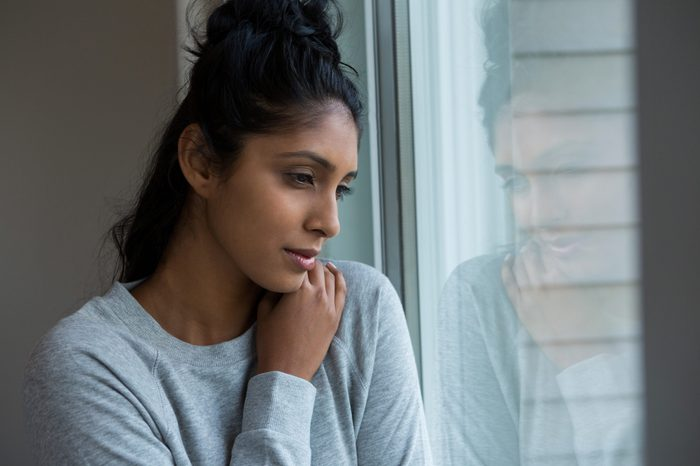 Thoughtful woman looking through window at home