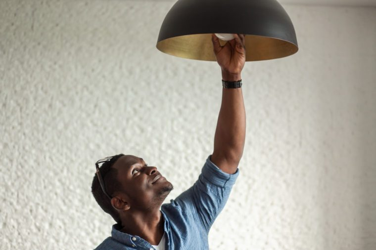 African man changing light bulb in coffee shop , installing a fluorescent light bulb