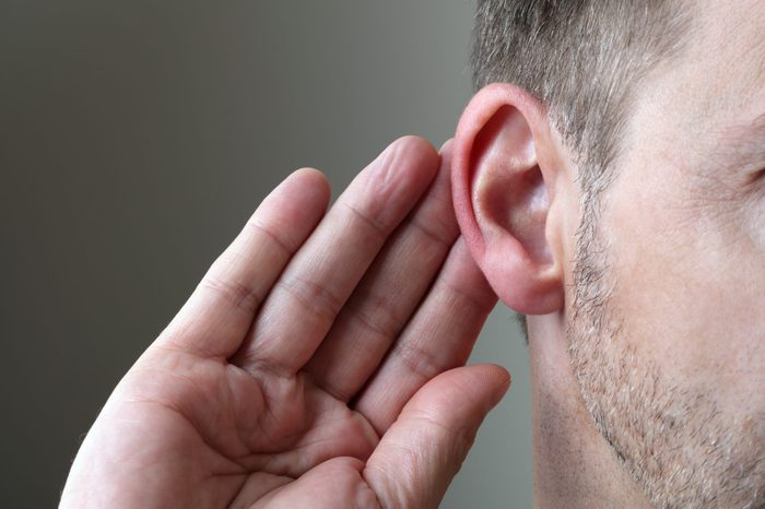 Close up on hand and ear listening for a quiet sound or paying attention