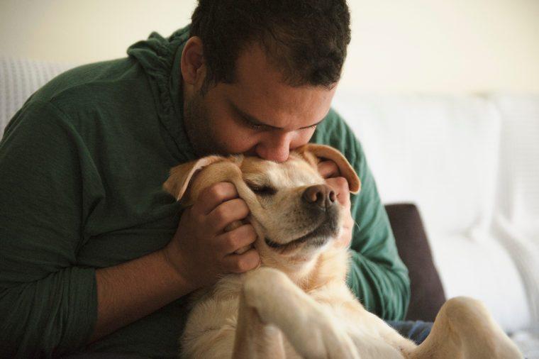 man kisses a dog