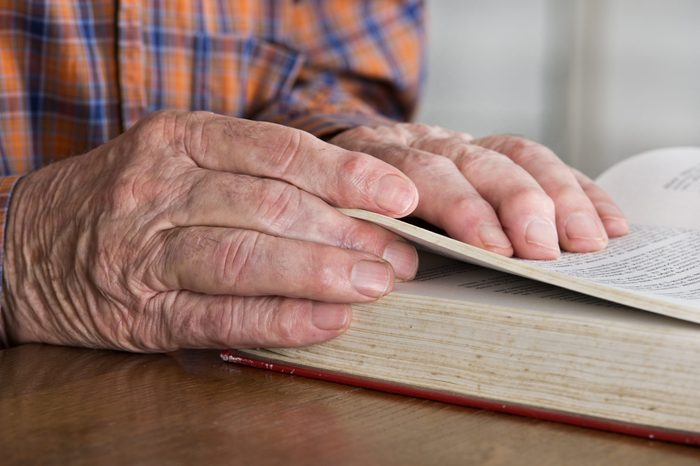 Close up of old man's hands who's reading book