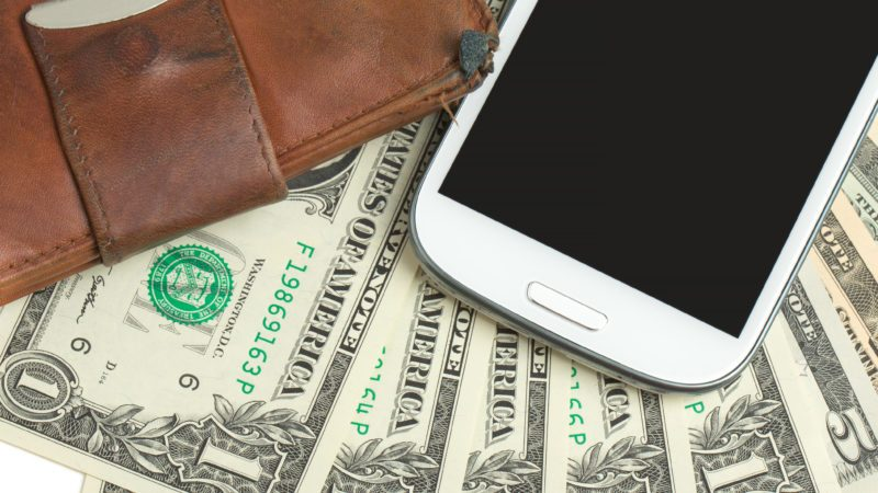 cellphone and money on white, money concept, expensive bill