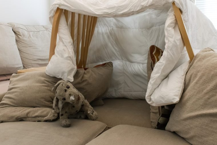 A pillow fort made of blankets chairs with a stuffed animal in the living room. Great for kids watching movies