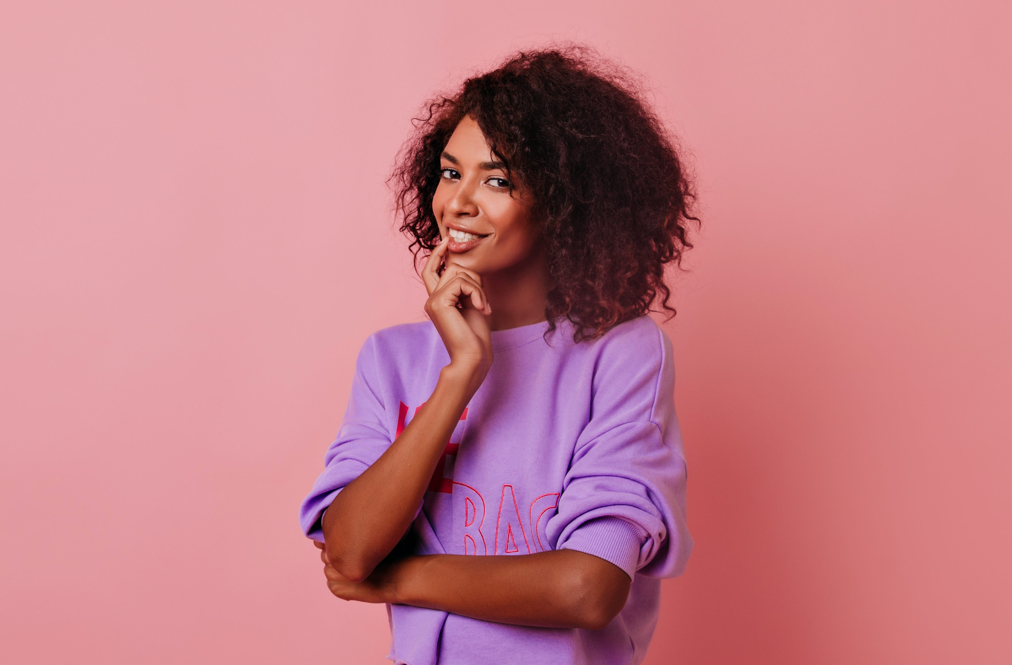Curious pretty woman with curly hairstyle standing on rosy background. Portrait of joyful african female model gently smiling to camera.