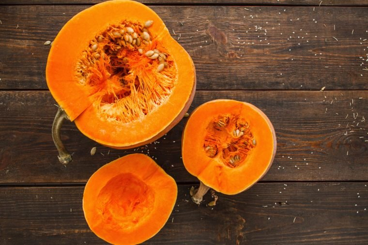 Set of orange pumpkins on wood flat lay free space. Fresh cut squashes on wooden table, country autumn background. Seasonal, harvest, fall, organic food, dieting, healthy food concept