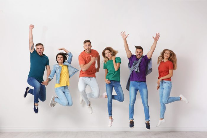 Group of young people in jeans and colorful t-shirts jumping near light wall