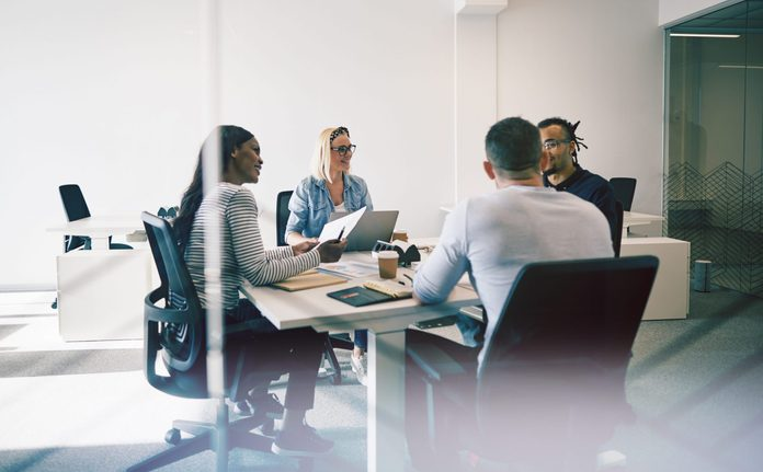 Smiling group of diverse coworkers talking together during a meeting around a table inside of a glass walled office