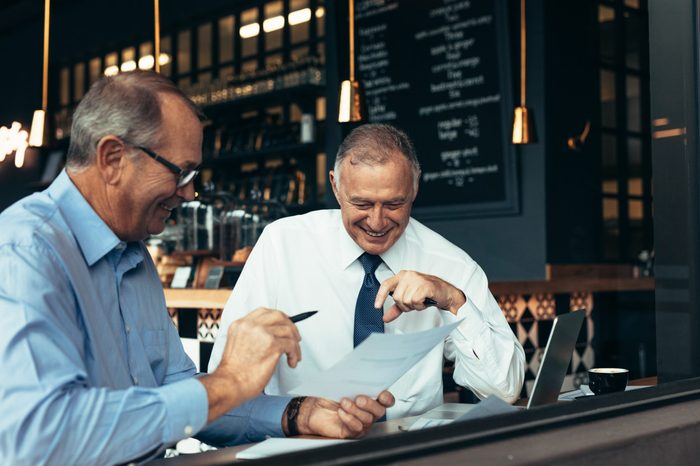Happy senior business people talking over few reports at cafe. Two business partners reviewing contract papers at a restaurant.
