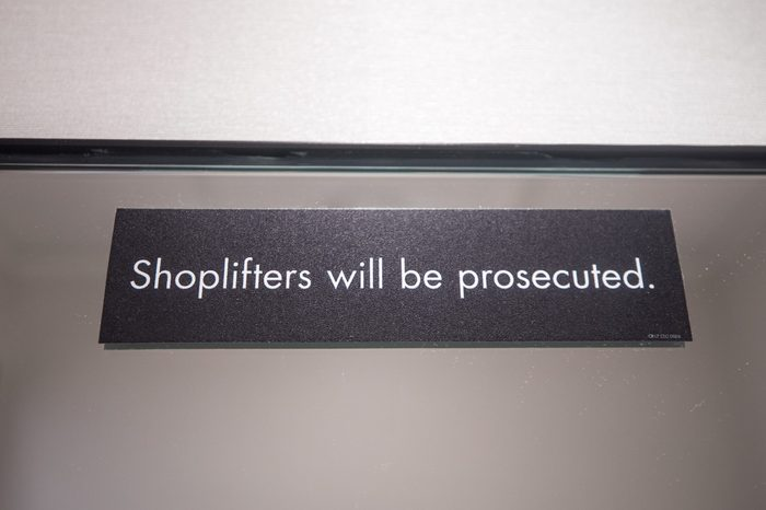 """A sign in a changing room of a retail store reads """"shoplifters will be prosecuted"""" as a warning to potential thieves."""