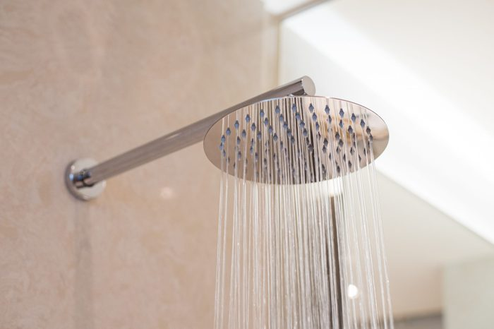 Shower turned on, overhead ceiling shower faucet head closeup.