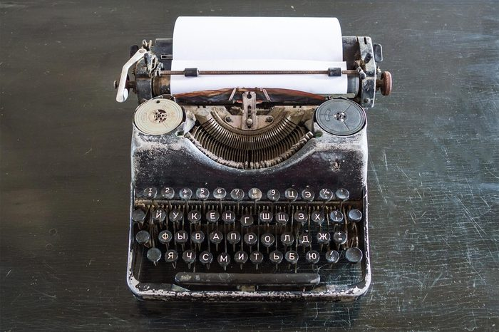An old typewriter on an old black table with a sheet of paper.