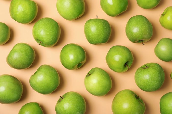 Many juicy green apples on color background, top view