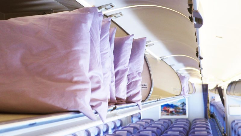 Spare pillows in the airplane overhead compartment, selective focus.