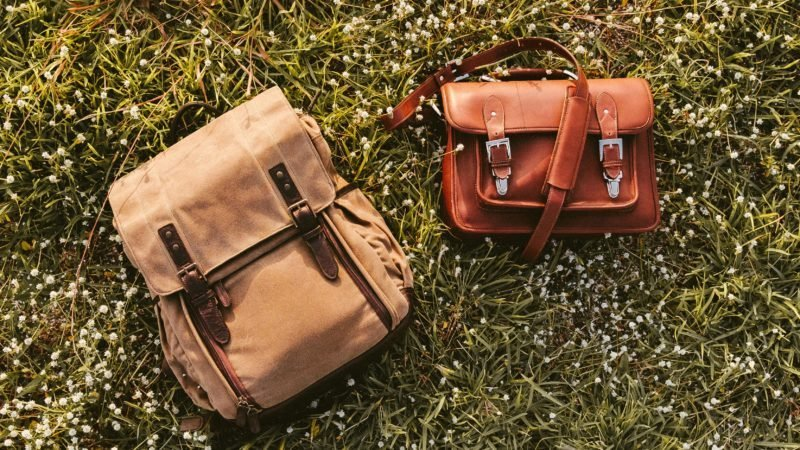 Fine Quality Handmade Leather Messenger Camera Bag and Backpack Flat Lay on Grass