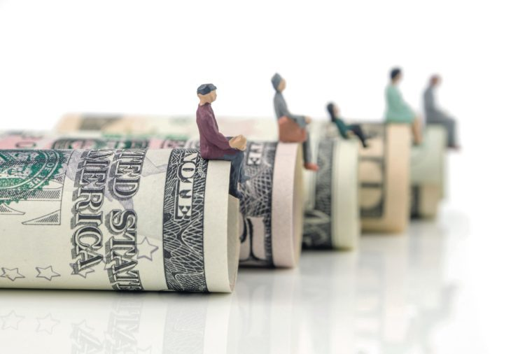 miniature figurines sitting on the edge of us dollar banknotes on white background