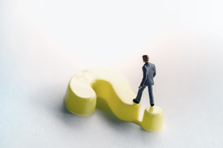 Business and working concept. Businessman miniature figure walking on yellow plastic question mark symbol