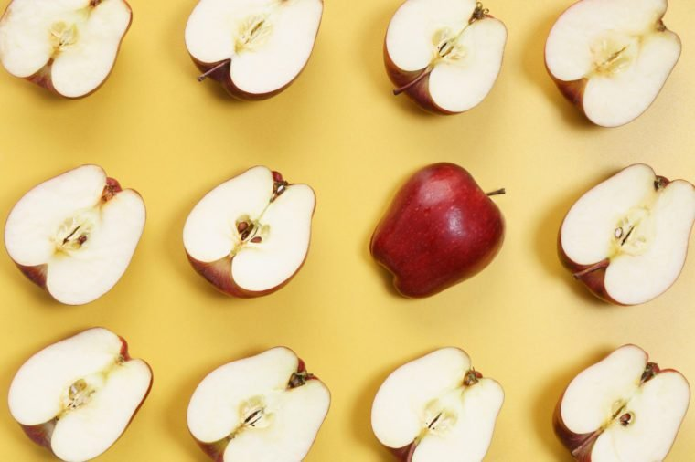 sliced red apples in a row on yellow background