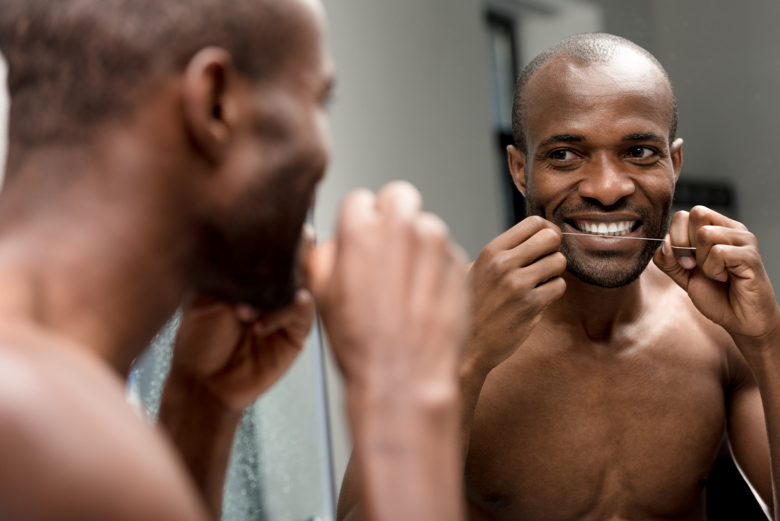 smiling young african american man holding dental floss and looking at mirror in bathroom