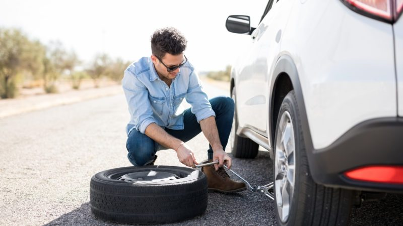 Handsome young man lifting the car on the jack for changing flat tire on the road